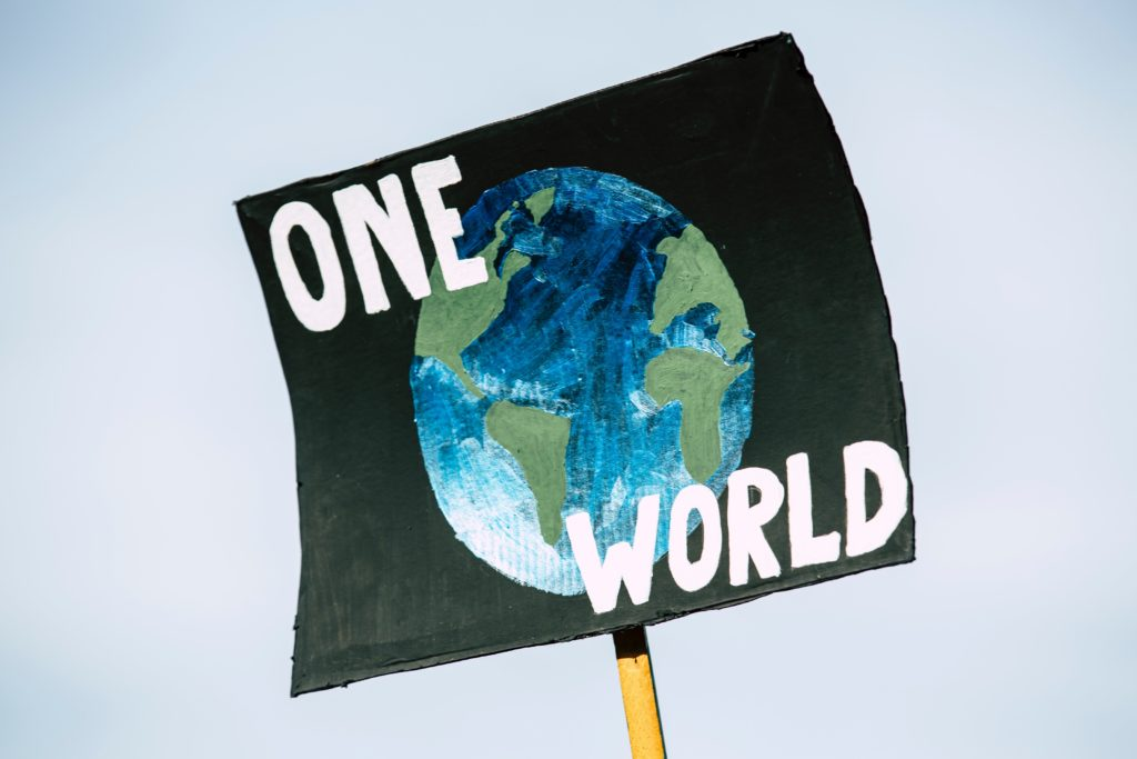 Painting of the globe on a sign with caption 'one world'